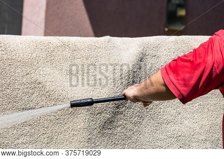 Close Up Of Washing Carpets With High Pressure Washer. Cleaning The Carpet With A Gun For Washing Hi