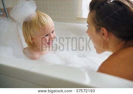 Mother and baby taking bath and playing with foam poster