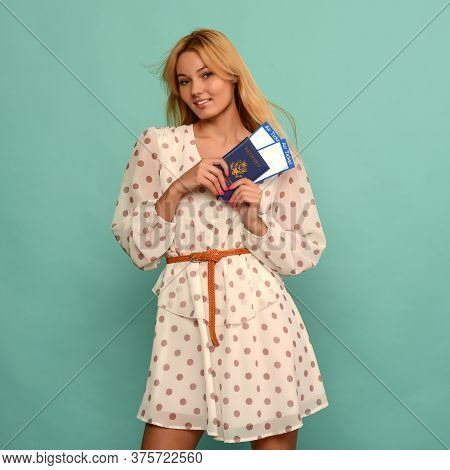 Joyful Young Woman In Polka Dot Dress Is Holding Airline Tickets With A Passport On A Blue Backgroun