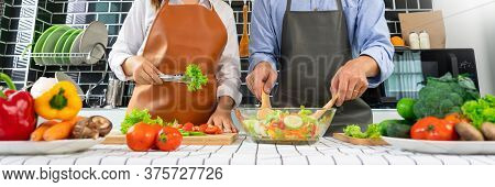 Happy Couple Having Fun Standing In Kitchen At Home Preparing Vegetable Salad Husband And Wife Veget