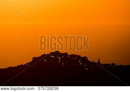 Sant'antonino Silhouetted By Orange Glow At Sunset