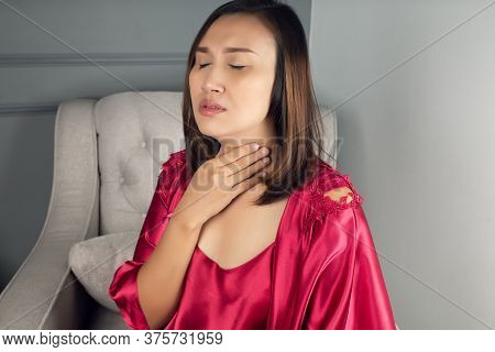 Sore Throat Pain Symptoms. Throat Infection. A Woman Wearing A Satin Nightgown And Red Robe Sufferin