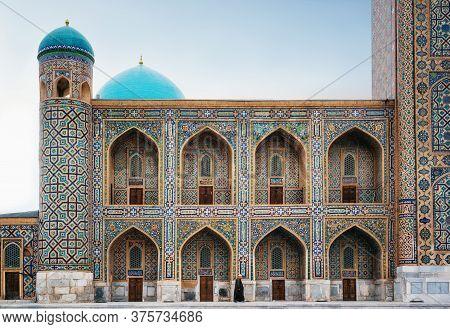 Man In Black Wear Walks Along Tilya-kori Madrasah In Historic Registan Square, Samarqand, Uzbekistan