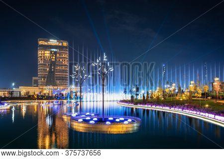 Tashkent, Uzbekistan - 30 October, 2019: Beautiful Dancing Fountain Illuminated At Night With Reflec