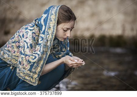 The Girl In The Indian Sari Sits At The Small River And Drinks From Hands