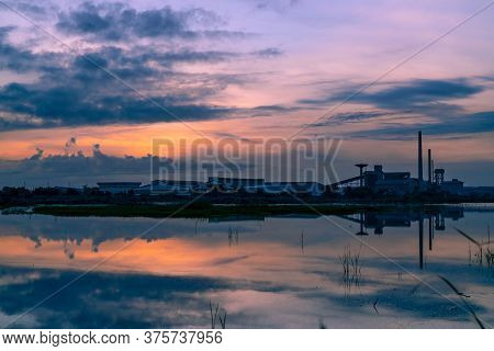 Landscape Of Factory Industry Buildings With Dark Blue And Orange Sunset Sky Reflection On Water In