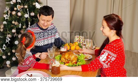 Family Joins Hands And Congratulates For Happy New Year Telling Wishes At Festive Supper Near Christ