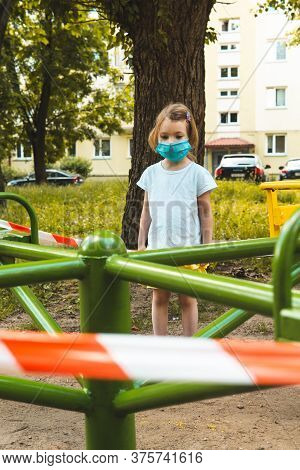 Little Cute Girl In Face Mask At Closed Childrens Playground. Covid-19 Security And Protection Measu