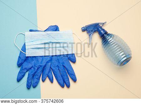Blue Gloves And Reusable Textile Mask, Blue Bottle For Disinfector On A Beige-blue Background, Top V