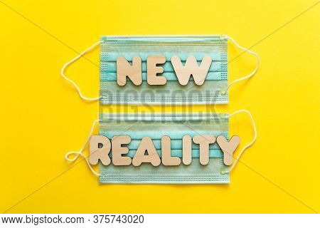 New Reality Words On Protective Face Masks On Yellow Background. Post Covid-19 Pandemic Changes, New