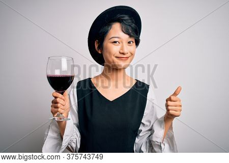 Young beautiful asian sommelier girl drinking glass of red wine over isolated white background happy with big smile doing ok sign, thumb up with fingers, excellent sign