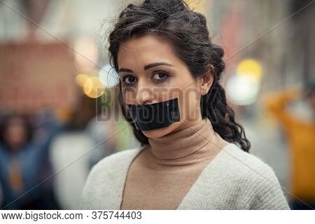 Portrait of young latin woman with black tape on mouth fighting against domestic violence. Abused girl tired of harassment looking at camera. Sad speechless indian woman with makeup running.