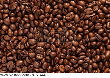 Roasted coffee beans background. Golden coffee beans freshly roasted and ready to prepare a black espresso coffee.