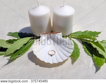 Seashell With Ring In It On White Table With Candles And Decorations. Engagement Ring With Diamonds