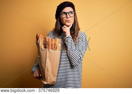 Young beautiful brunette french woman wearing beret holding paper bag with baguettes serious face thinking about question, very confused idea