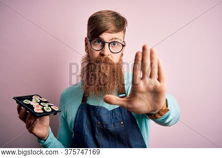 Redhead Irish cook man with beard holding maki sushi tray over isolated background with open hand doing stop sign with serious and confident expression, defense gesture