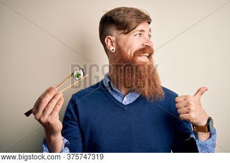 Redhead Irish man with beard eating green maki sushi using chopsticks over yellow background pointing and showing with thumb up to the side with happy face smiling