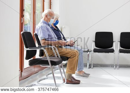 Senior Couple Sitting With Face Masks In A Bright Waiting Room Of  A Hospital Or An Office