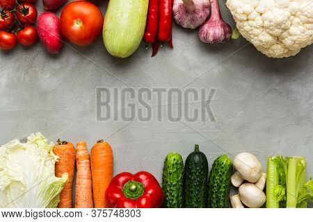 Various Raw Vegetables On A Gray Background With Copy Space In The Center. Zucchini, Cucumber, Chili