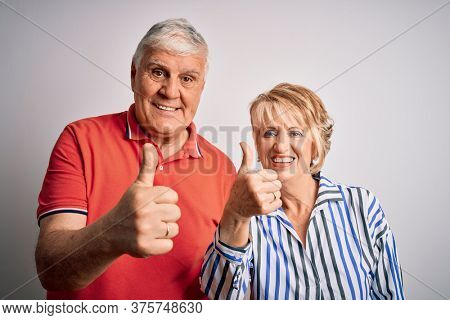 Senior beautiful couple standing together over isolated white background success sign doing positive gesture with hand, thumbs up smiling and happy. Cheerful expression and winner gesture.