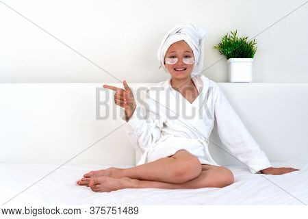 Teenager Girl In A Bathrobe And A White Towel Shows On Empty Space. Young Attractive Little Girl Wit