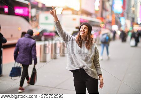 Young beautiful woman smiling happy and confident. Standing with smile on face and hand up calling cab at the city