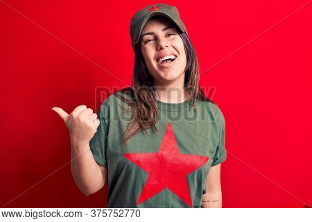 Young beautiful brunette woman wearing cap and t-shirt with red star communist symbol pointing thumb up to the side smiling happy with open mouth