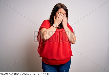 Beautiful brunette plus size woman wearing casual red t-shirt over isolated white background rubbing eyes for fatigue and headache, sleepy and tired expression. Vision problem
