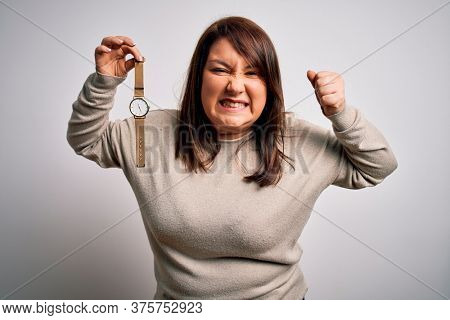 Beautiful brunette plus size woman holding wristwatch over isolated white background annoyed and frustrated shouting with anger, crazy and yelling with raised hand, anger concept