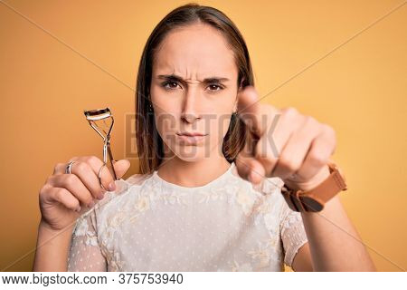Young beautiful woman using eyelash curler standing over isolated yellow background pointing with finger to the camera and to you, hand sign, positive and confident gesture from the front