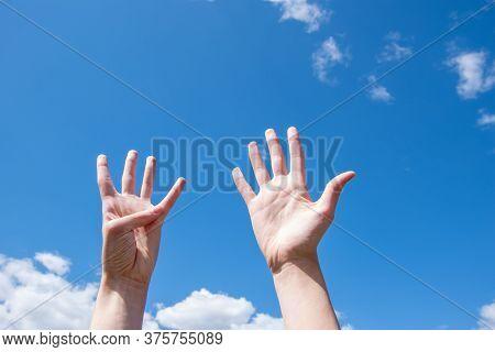 Close-up Of Female Hands Showing Nine Fingers On A Blue Sky Background. Number Nine In Sign Language