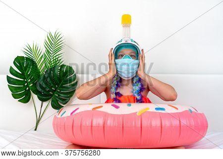 Little Girl In Medical Mask Imitates Vacation At Home Quarantine. Domestic Tourism. Coronavirus Situ