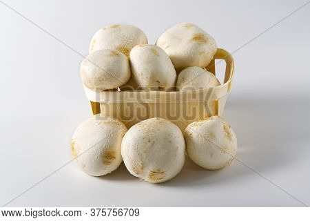 White Mushrooms Champignons In Wooden Basket On A Light Background. Close Up. Packed Champignons To
