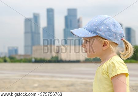 Profile Portrait Of A Blonde Little Girl Baby On A Background Of Skyscrapers. Little Kid In A Huge C