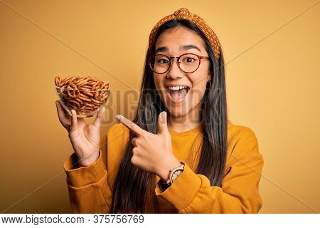 Young beautiful asian woman holding bowl with german baked pretzels over yellow background very happy pointing with hand and finger