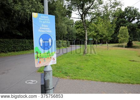 Swansea, Wales, Uk - July 10, 2020: Coronavirus Covid 19 Social Distancing Sign On A Lampost In Sing