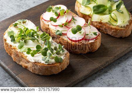 Tree Sandwich On Toast With Sundries Tomato, Fresh Radish Microgreens, Cream Cheese On Cutting Board