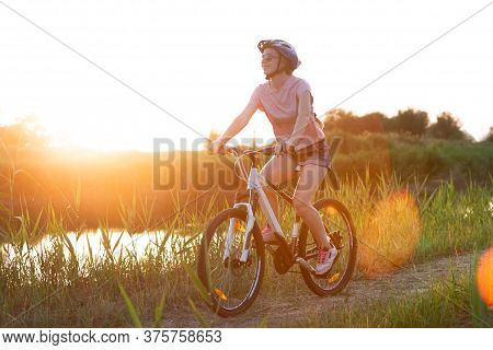 Nature. Joyful Young Woman Riding A Bicycle At The Riverside And Meadow Promenade. Inspired By Surro