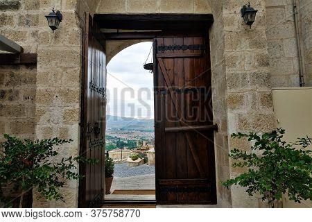 Doorway In Stone Wall. One Half Of The Wooden Door Is Open. Visible Pavement, Decorative Flowers. In