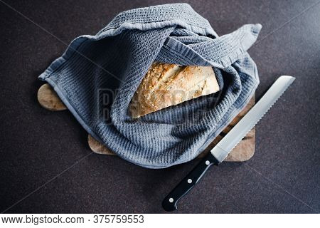 Simple Food Ingredients Concept, Homemade Sourdough Bread On Cutting Board Wrapped In Tea Towel On K