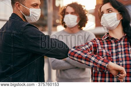Young Man And Woman In Medical Masks Looking At Each Other And Bumping Elbows While Meeting On City