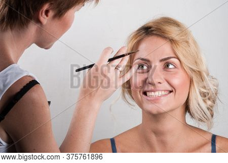 Close-up: A Professional Makeup Artist Does Glamorous Makeup For A Beautiful Blonde Behind The Curta