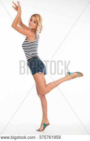 Full Length Portrait Of A Playing Young Girl In A Striped T-shirt And Shorts Isolated Over A White