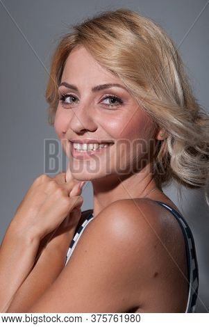 Portrait Of A Smiling Young Beautiful Woman Looking At The Camera On A Dark Gray