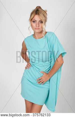 Portrait Of A Young Beautiful Woman In A Light Blue Dress Posing In The Studio