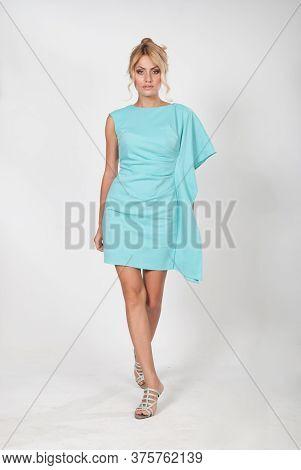 Portrait Of A Beautiful Sexy Woman In A Light Blue Dress Is Walking In The Studio On A Light Backgro