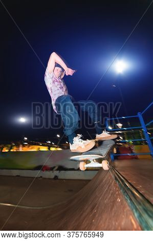 A Young Skater Does The Trick Of Sliding At Night In A Skatepark. The Concept Of Night Leisure And Y