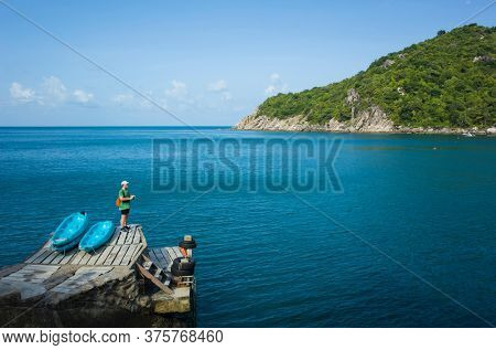 Tropical island vacation one man staying on bridge on Koh Tao Island looking on blue empty water of Mango Bay. Famous destination for travel holidays in Thailand