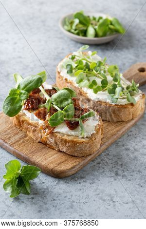 Two Sandwiches With Cream Cheese, Sundries Tomato, Fresh Radish Microgreen On Grey Background. Close