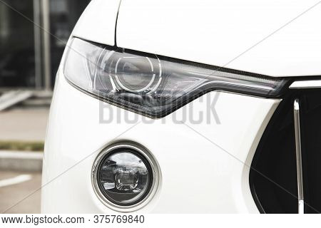Car Headlights. Luxury Headlights. Part Of A White Luxury Car Close Up.